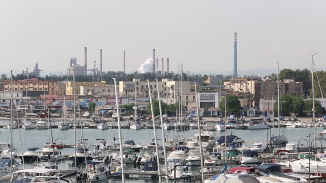 ILVA steel Plant fishermen repairing fishnets and views of the port and city in Taranto Italy on Tuesday May 22 2018
