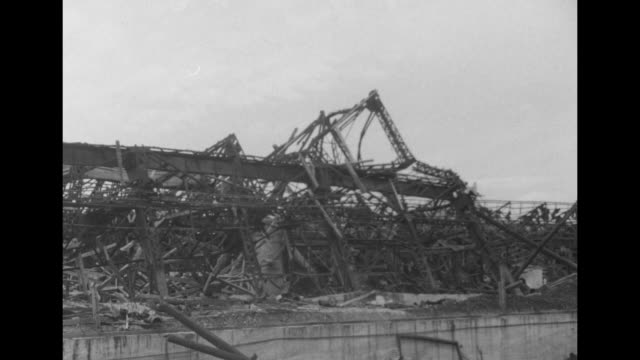 steel structure of factory twisted and crumpled, large pipes, few standing smokestacks, machinery in twisted piles, piles of burned machine parts /... - 鋼点の映像素材/bロール