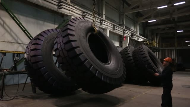 vídeos de stock, filmes e b-roll de steel wire cord passes through a machine during the calendering process to fabricate rubber tires at the belshina jsc tire factory in babruysk... - borracha material
