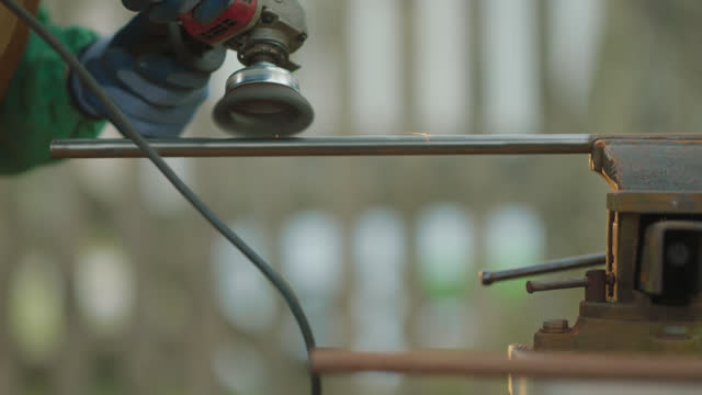 slo mo steel worker buffs the rust off a metal pipe with an angle grinder - metalwork stock videos & royalty-free footage