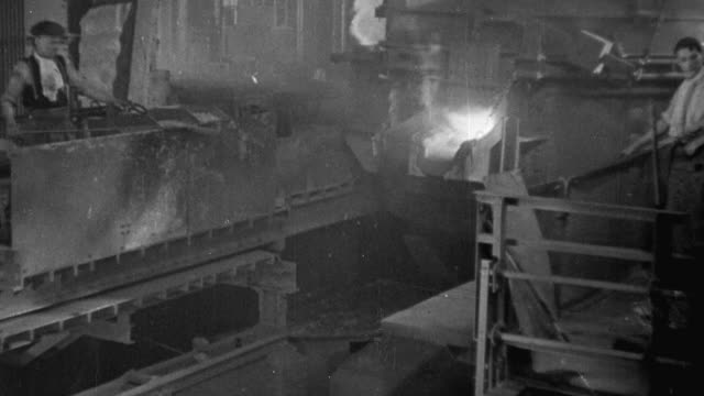 1940 montage steel worker gathering a sample for inspection / united kingdom - stahlwerk stock-videos und b-roll-filmmaterial