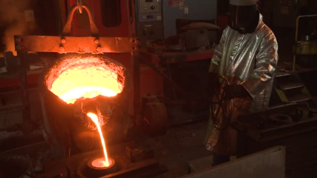 a steel worker in a fire-resistant suit stands near a pulley and pours molten steel into a cylinder. available in hd. - perdita video stock e b–roll