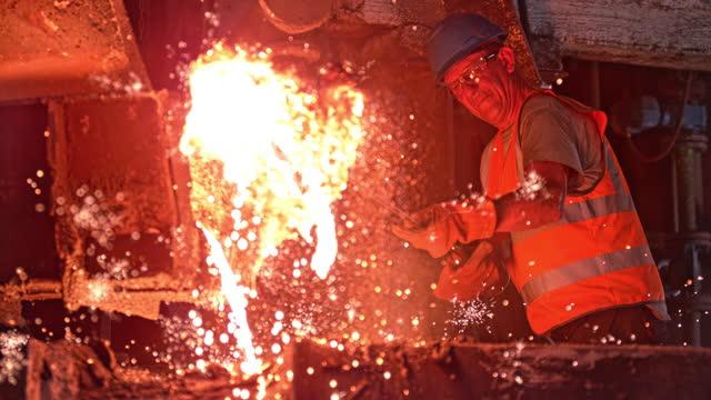 slo mo ld steel worker removing slag from the molten metal - 僅一成熟男士 個影片檔及 b 捲影像