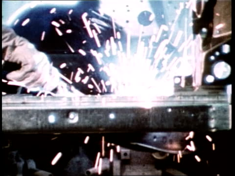 steel worker stokes a furnace as sparks fly; an auto worker welds car parts in a factory. - steel mill stock videos & royalty-free footage