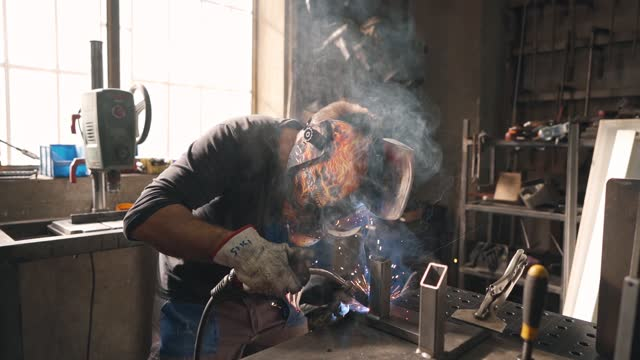 steel worker using a welding torch to attach a metal pipes into frame - welding helmet stock videos & royalty-free footage