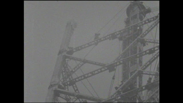 a steel worker walks across a girder on the tokyo tower construction site. - balkengerüst stock-videos und b-roll-filmmaterial