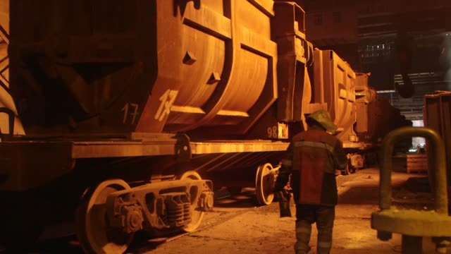 Steel worker walks past railway cars CU of smelter pouring metal and spitting sparks workers smoke as molten steel rains down pans out and over to...