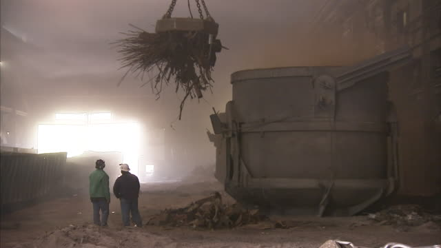 steel workers stand beneath a magnetic crane that deposits scrap metal into a cauldron. - steel stock videos & royalty-free footage