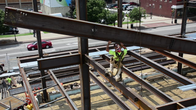 A steelworker grabs a swinging beam while balancing on narrow steel at a 12story commercial construction site in Columbus Ohio
