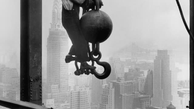 a steelworker hangs from a crane hook above manhattan streets at the construction site of the empire state building. - empire state building video stock e b–roll