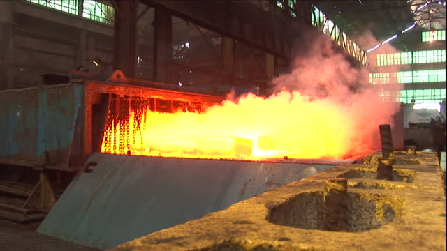 a steelworker throws a chemical agent on a hot steel ingot. - opificio video stock e b–roll