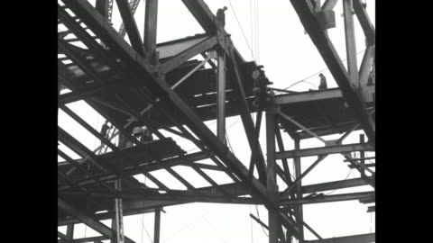 steelworkers perched on girders with a construction crane hoisting steel beams into place atop building / note: exact month/day not known - hoisting stock videos & royalty-free footage