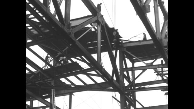 vs steelworkers perched on girders with a construction crane hoisting steel beams into place atop building / note exact month/day not known - rockefeller center video stock e b–roll