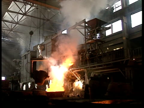 vídeos de stock, filmes e b-roll de wa steelworks factory with molten metal flowing from smelter - fornalha