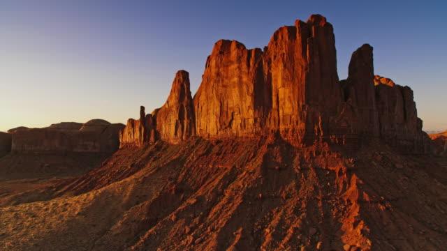 vídeos de stock e filmes b-roll de aerial steep butte slopes shining in the morning sun - monument valley