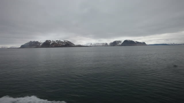 Steep cliffs along Billefjorden Fiord at Dickson Land on Spitsbergen island, seen from a sailing boat