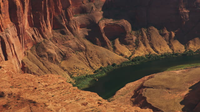 aerial steep cliffs surrounding the colorado river at the horseshoe bend in arizona, usa - rock formation stock videos & royalty-free footage