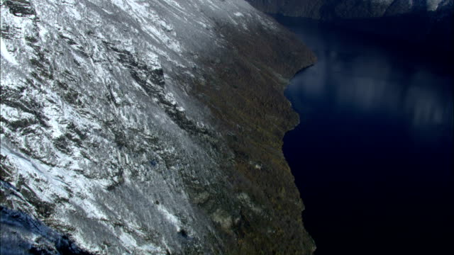 Steep rock cliffs and forested slopes line the scenic coast of Norway. Available in HD.