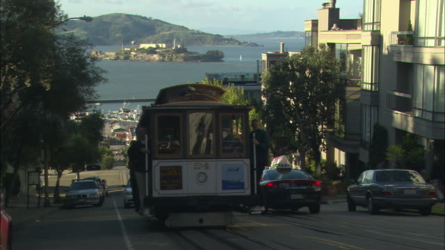 ws steep san francisco street busy with car traffic and trolley cars, alcatraz island in background / california, usa - san francisco bay stock videos & royalty-free footage