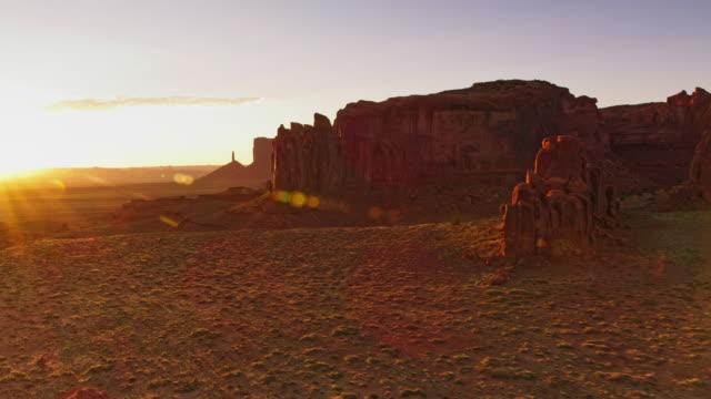 aerial steile hänge der buttes und mesas im monument valley national park von der morgensonne beleuchtet - tafelberg felsformation stock-videos und b-roll-filmmaterial