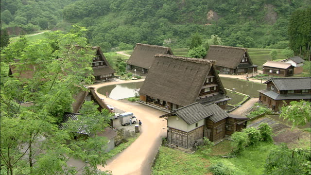 Steep thatched roofed houses occupy a lush hamlet in Gokayama, Japan.