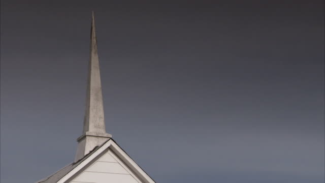 A steeple of Lawler Baptist Church stands against a dark grey sky. Available in HD.