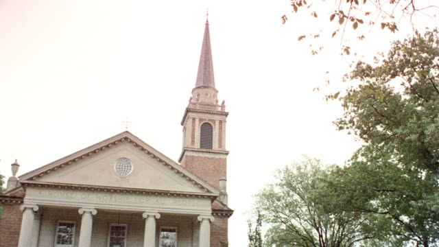 a steeple overlooks the lawn of a church. - steeple stock videos & royalty-free footage