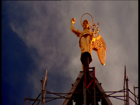 steeple under construction mounted with golden angle glistening in sunlight light clouds float past in background las vegas - steeple stock videos & royalty-free footage
