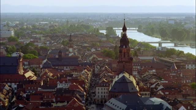 steepled buildings crowd the banks of the neckar river in heidelberg, germany. - ハイデルベルク点の映像素材/bロール
