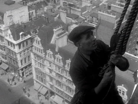 a steeplejack carefully lowers himself down to one of big ben's clock faces 1953 - turmarbeiter stock-videos und b-roll-filmmaterial