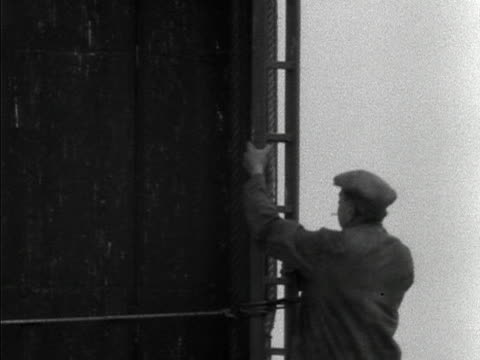 a steeplejack climbs nelson's column to clean the statue in preparation for the coronation 1953 - turmarbeiter stock-videos und b-roll-filmmaterial