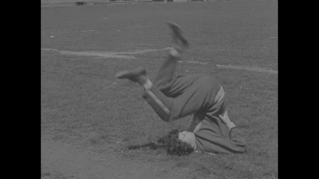 vídeos de stock e filmes b-roll de stella walsh a/k/a stanislawa walasiewicz lies on the grass demonstrating stretching exercises by pedaling her legs in the air she pulls her knees to... - hermafrodita