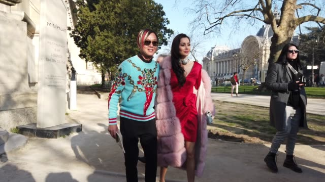 stephen hung wears aviator mirro sunglasses, a black scarf, a blue wool pullover with embroidered multicolor jewelry ; deborah valdez hung wears a... - paris fashion week - haute couture spring/summer 2020点の映像素材/bロール