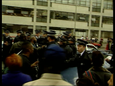 Inquiry bC4N ITN ENGLAND London Elephant Castle Ext GVs Police trying to restrain angry crowds outside inquiry building Five suspected men Jamie Neil...
