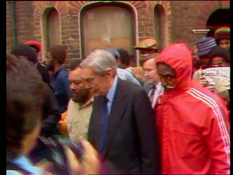 stephen lawrence murder inquiry report made public; lib brixton ext lord scarman being escorted through crowd by black man in red anorak - レインコート点の映像素材/bロール