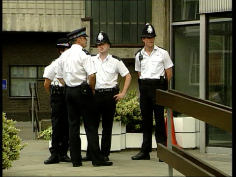 Policeman cleared of charges ITN ENGLAND London LA Police officers outside building where disciplinary hearing was held into case of Detective...