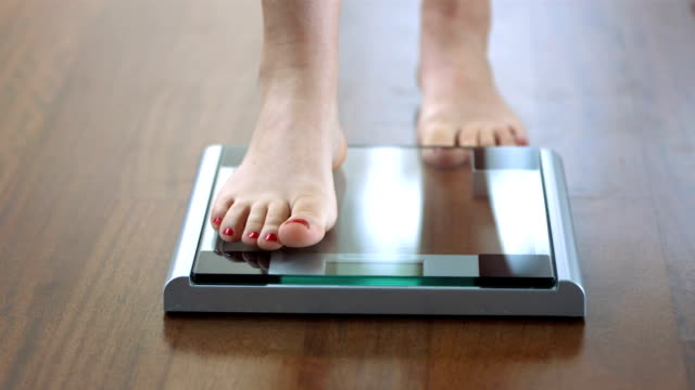 hd dolly: stepping on the bathroom scale - weight scale stock videos & royalty-free footage