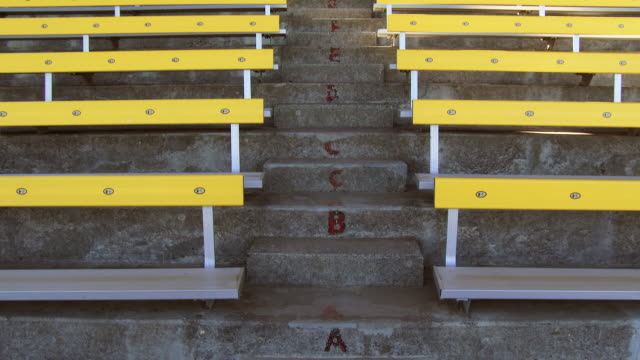 Steps and empty bleachers in a stadium, tilt up