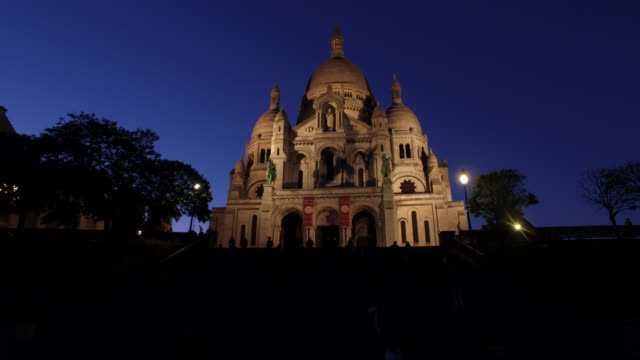 steps in front of the illuminated facade of the basilica of the sacred heart, at night. may 6, 2020 in paris, france. - cathedral stock videos & royalty-free footage