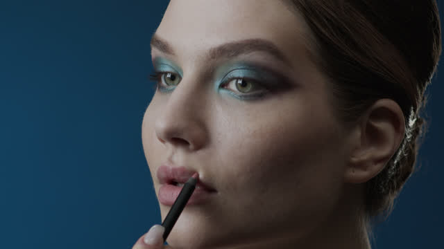 passaggi di make-up applicabili. primo-up di una faccia da ragazza, applicando una matita bordeaux sulle labbra. - super slow motion video stock e b–roll