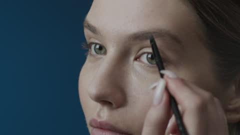 vídeos de stock, filmes e b-roll de etapas de maquiagem se candidatando. close-up de um rosto de menina, desenhando sobrancelhas, usando um pincel de maquiagem. - sobrancelha