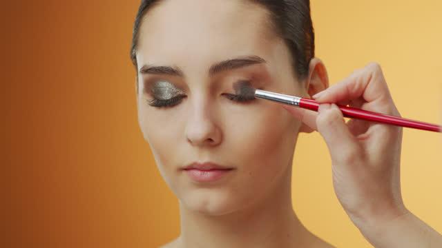メイクアップ適用のステップ。メイクアップアーティストのまぶたがメイクアップブラシで茶色の影を適用する女の子の顔のクローズアップ。 - アイシャドウ点の映像素材/bロール