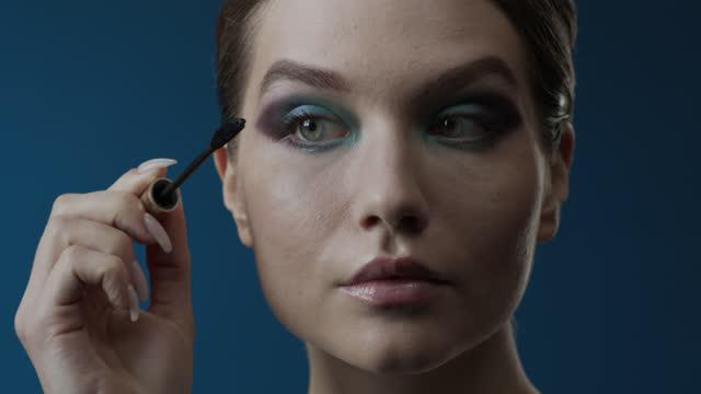 vídeos de stock, filmes e b-roll de etapas de maquiagem se candidatando. close-up de uma garota com olhos verdes aplica rímel com um pincel. - olhos verdes