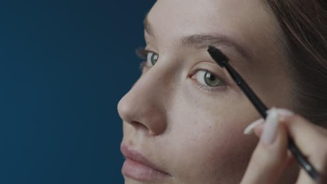 vídeos de stock, filmes e b-roll de etapas de maquiagem se candidatando. close-up do rosto de uma garota penteando as sobrancelhas com um pincel de maquiagem. - sobrancelha