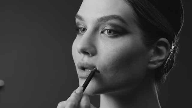 steps of make-up applying. close-up of the face of a woman who paints her lips with a lip liner. black and white video. - lip liner stock videos & royalty-free footage