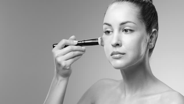 メイクアップ適用のステップ。女の子はメイクアップブラシで頬骨に基礎を適用します。白黒ビデオ。 - メイクアップブラシ点の映像素材/bロール