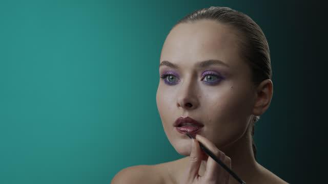 メイクアップ適用のステップ。青い目をした女の子は化粧をします - 彼女はメイクアップブラシを使用して暗い口紅で彼女の唇をペイントします。 - 絵画モデル点の映像素材/bロール