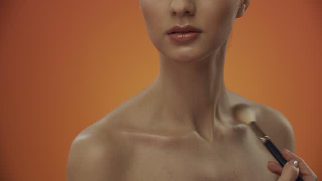 schritte der make-up-anwendung. make-up-künstler verwendet eine make-up-pinsel, um den highlighter auf das mädchen schlüsselbein auftragen. - the human body stock-videos und b-roll-filmmaterial