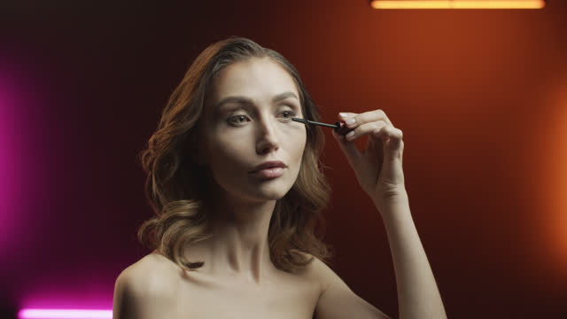 schritte der make-up-anwendung. junge frau malt wimpern mit mascara mit einem make-up-pinsel. - wimper stock-videos und b-roll-filmmaterial