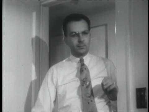 b/w 1954 stern man with eyeglasses opening door - 1954年点の映像素材/bロール